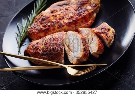 Skinless Boneless Chicken Breasts Baked With Spices Served On A Black Plate With Golden Cutlery And