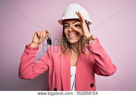 Young beautiful brunette architect woman wearing safety helmet hoding key of house with happy face smiling doing ok sign with hand on eye looking through fingers