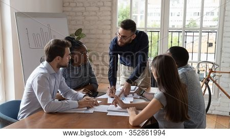 Focused Diverse Group Listening Arab Ceo During Briefing In Office