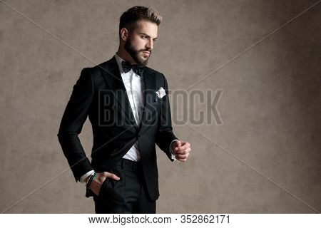 Bothered groom frowning with his hand in his pocket while wearing tuxedo and walking on wallpaper studio background