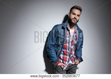 Tough fashion model holding both hands in his pockets while standing on gray studio background