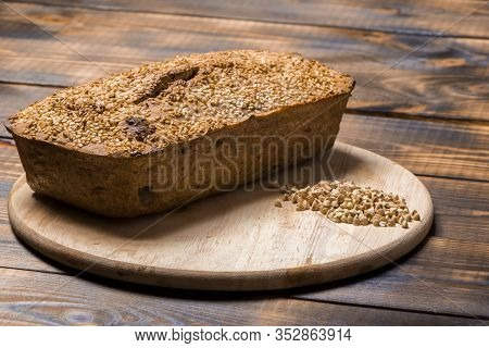 A Loaf Of Freshly Baked Buckwheat Bread Lies On A Round Kitchen Board On A Brown Wooden Table. A Han