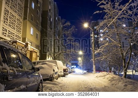 Snow-covered City Courtyard In The Late Evening. Magical Landscape. Snow-covered Cars Parked Along H