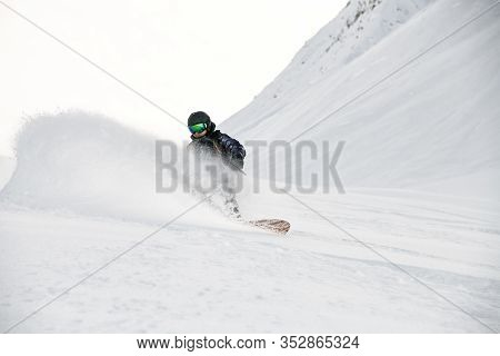 Freerider In Full Equipment Rides On A Snowboard In Mountains