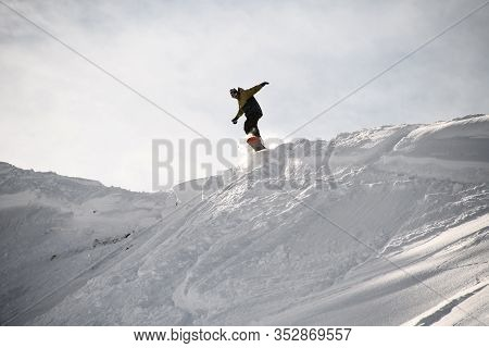 Freerider In Anorak Jumping On A Snowboard In Mountains