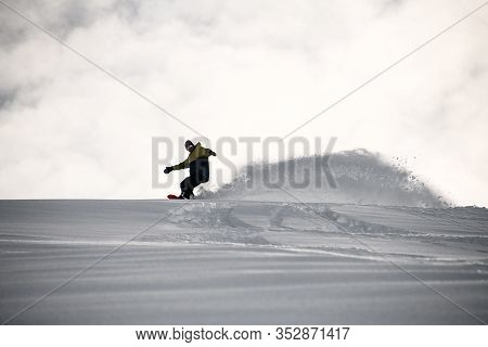 Freerider In Full Equipment Sliding On A Snowboard In Mountains
