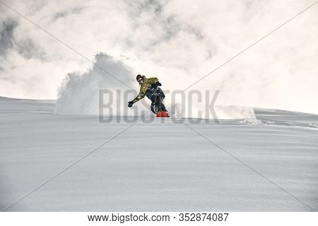 Freerider On A Snowboard Slipping On A Snowy Mountain Side
