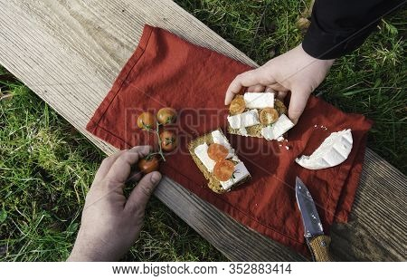 Outdoor Meal On Green Grass In Sunlight. People Hands Grabbing Food At Picnic, On A Wood Plank. Toma