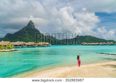 Polynesian hula dancer dancing on Bora Bora beach at luxury overwater bungalows hotel resort at luau show party for tourists. Tahiti, French Polynesia.