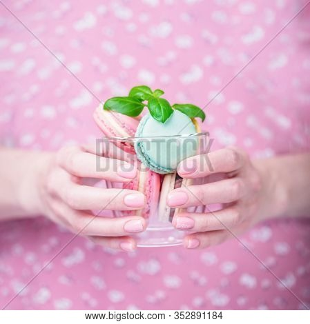 Beautiful Female Hands Holding Transparent Cup With Colored Macaroons. Manicure With Pink Color Nail