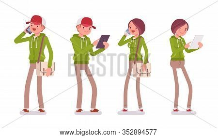 Young Man And Woman Wearing A Hoodie Jacket Standing With Smartphone, Tablet. Cute Smart People In C