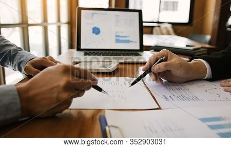 Business Partnership Pointing To The Graph Of The Company Financial Statements Report And Profits Ea