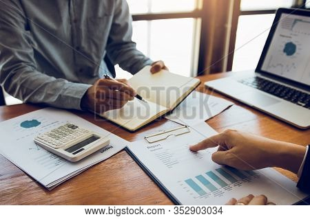 Two Business Partnership Coworkers Analysis Strategy With Discussing A Financial Planning Graph And