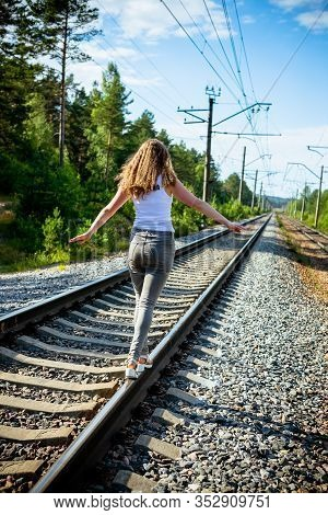 The Back Of Traveler Hipster Girl In Casual Clothes Walking Along The Railroad To The Destination. T