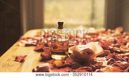 Glass Essential Oil Bottle And Roses Petals On Wooden Surface, Toned Warm, Selected Focus
