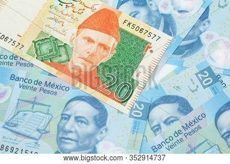 A Close Up Image Of An Orange And Green Twenty Pakistani Rupee Bank Note With Mexican Twenty Peso Ba