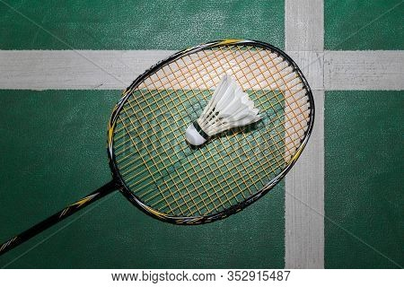 Top View Of White Badminton Shuttlecock And Racquet On Wooden Floor.