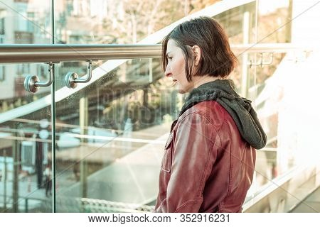 Brunette Woman With Red Leather Jacket Looking Through The Window Of A Train Station. Expectation Co