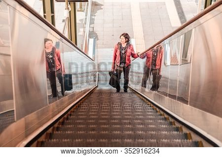 Brunette Woman With Red Leather Jacket Using Escalator At The Train Station In The Morning Light.