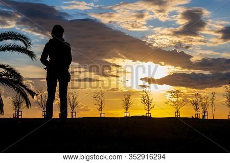 Silhouette Of A Slim Woman Watching The Sunset In The Park. Beautiful Dramatic Sky With Clouds.