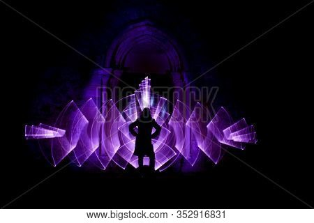 Silhouette Of A Woman In Front Of An Arch Carved In Stone. Curved Abstract Shape Made With A Light S