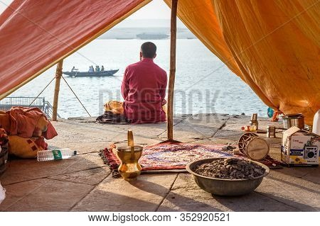 Varanasi, India - March 18, 2019: Hindu Priest Sits Inside Of His Tent Looking At Ganga River In Var