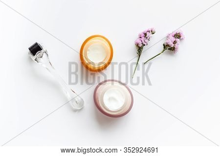 Cosmetologist Tools. Dermaroller, Creams Near Leaves And Flowers On White Background Top-down