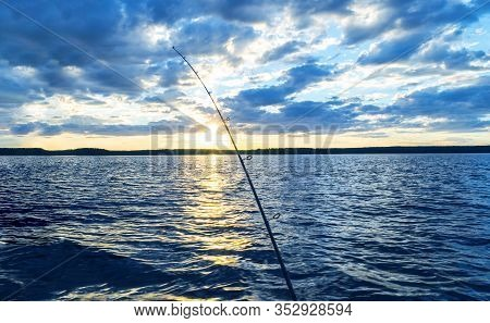 Fishing Rod Silhouette During Sunset. Fishing Pole Against Ocean At Sunset. Fishing Rod In A Saltwat