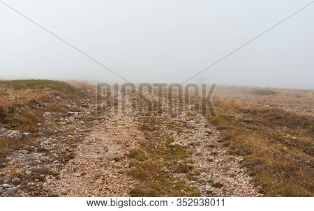 Autumnal Landscape With Empty Medieval Rocky Road In Fog On Babuhan Yaila Natural Reserve,  On Crime