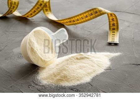 Whey Protein Powder In Plastic Scoop Near Measuring Tape On Grey Background
