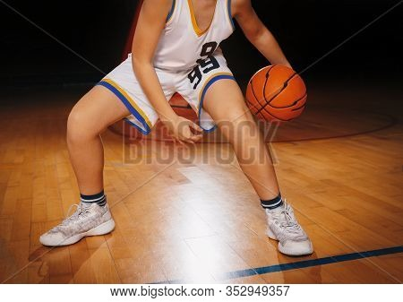 Kids Basketball Player On A Game. Male Elementary School Basketball Player Playing Game And Bouncing
