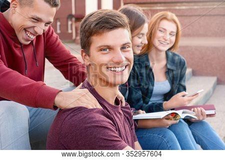 Two Teenage Boys Having Fun While Studing Against Girls Near University
