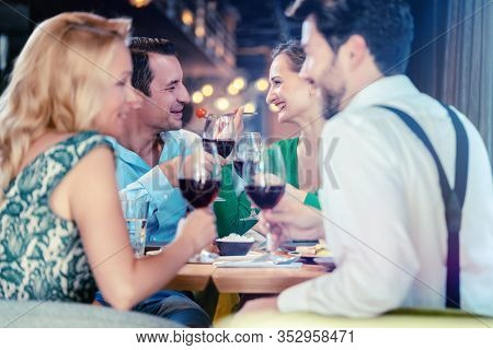 People in an upscale restaurant eating and drinking red wine