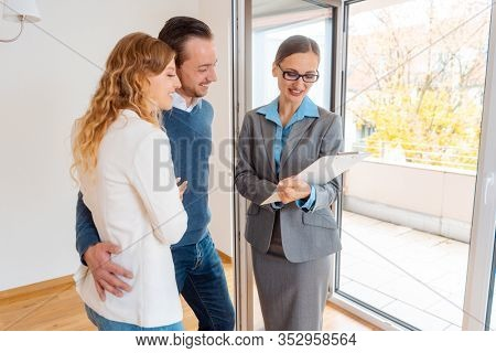 Landlady or realtor woman showing lease agreement to new tenants