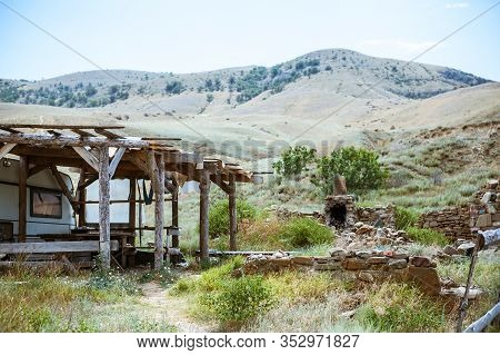 Old Ruined Log House And Stone Stove In The Yard In The Crimean Steppe On A Background Of Mountains