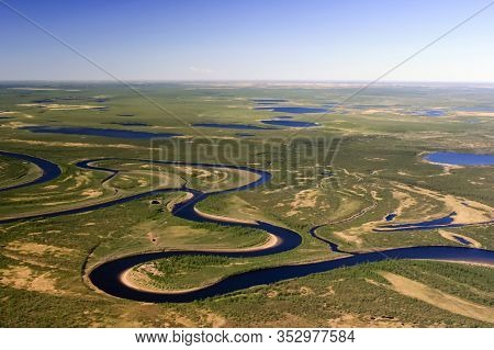 Nature Of The Northern Tundra Of The Taimyr Peninsula View From A Helicopter. Rivers, Lakes And Swam
