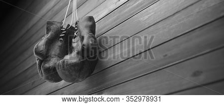 Old Boxing Gloves Hang On Nail On Wooden Wall With Copy Space For Text. High Resolution 3D Rendering