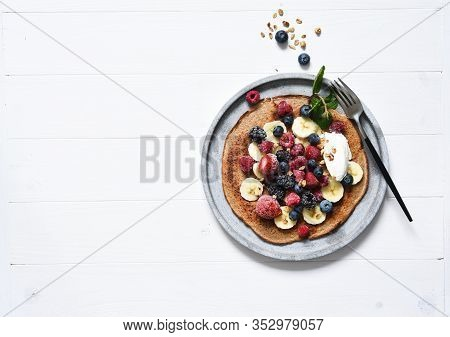 Crepe With Berries And Yogurt For Breakfast. Breakfast On The Kitchen Table Top View.
