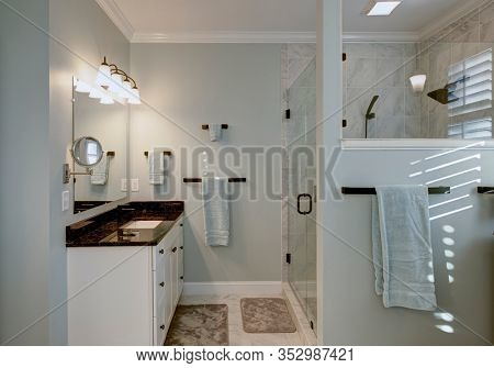 Beautiful luxury bathroom with marble and granite and stand alone glass shower.