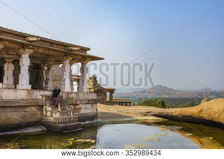 Girl Travelers Visiting The Ruins Of Hampi. The Famous Place Of Historical Heritage Of India. The Gr