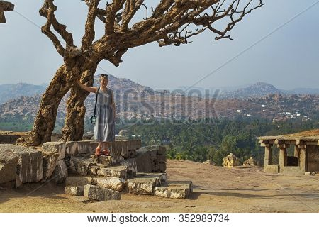 Tourist Girl Near An Ancient Building With A Tree. The Group Of Monuments At Hampi Was The Centre Of