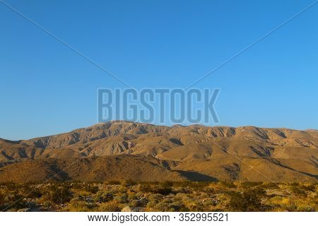 A Blue Sky And Rolling Desert Mountains In The Horizon