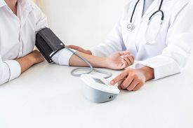Doctor Using Blood Pressure Monitor And Stethoscope Checking Measuring Arterial Blood Pressure On Ar