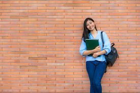 Asian Smiling Woman Student Holding Book Posing On Brick Background In Campus. Happy Teen Girl High