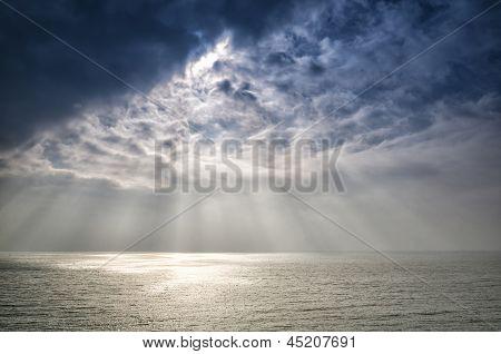 Beautiful inspirational sun beams over ocean on cloudy day