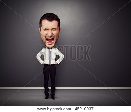 full-length picture of angry businessman with big head over dark background