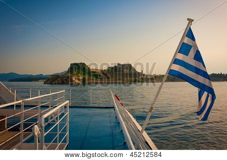 Corfu Castle And Greek Flag Pictured In Sunset From A Boat