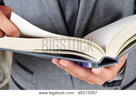 a man wearing a suit reading a book