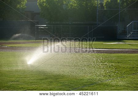 Baseball field sprinkler waters the grass pointed right