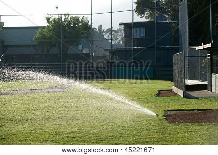 Baseball field sprinkler waters the grass pointed left